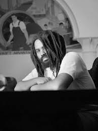 Mumia. FOTO Lou Jones. Arms folded on table